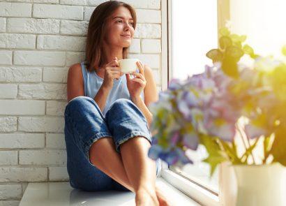 A woman enjoying a mug of tea, healthy with well-balanced hormones
