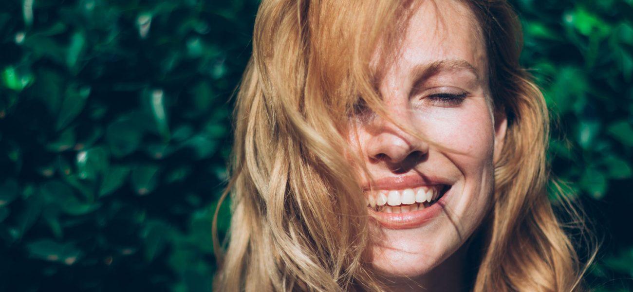 Woman smiling in the sunshine, enjoying vitamin D